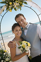 Bride and Groom under archway on beach (portrait)