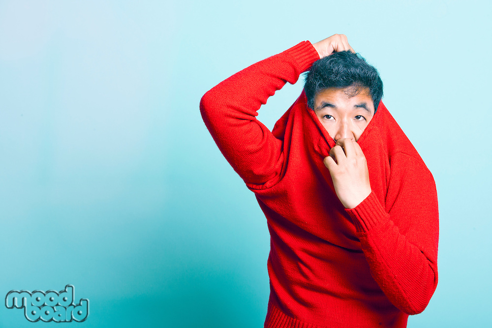 Young Asian Man trying to take of Red Sweater