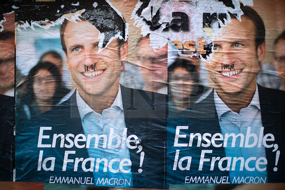 © Licensed to London News Pictures . 06/05/2017 . Paris , France . Flyers for Macron pasted to street furniture , on which someone has drawn toothbrush moustaches , in the Saint-Ouen district of Northern Paris . The electorate are voting in the final round of the French election today (7th May 2017) . Emmanuel Macron's En Marche and Marine Le Pen's Front National are competing for the Presidency . Photo credit: Joel Goodman/LNP