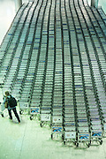Generic shot of traveller collecting a trolley from hundreds of luggage trolleys at an airport