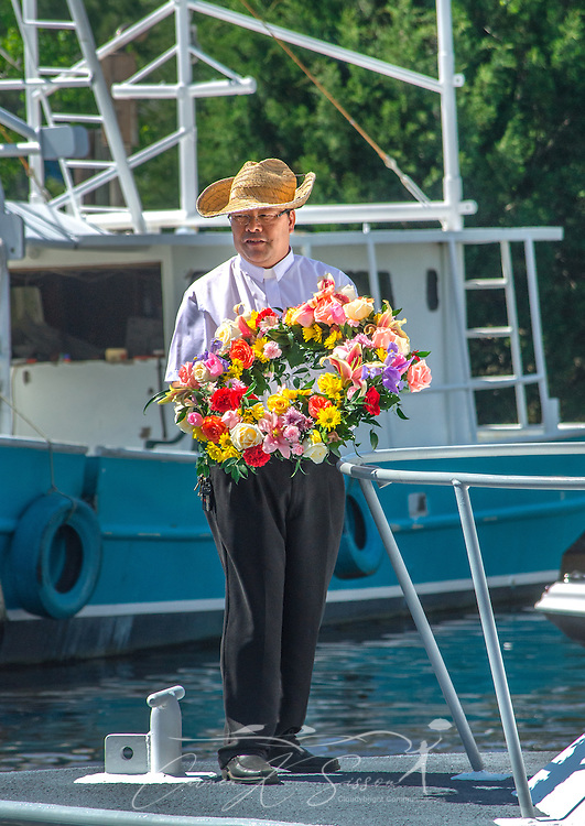 The Rev. Bieu Nguyen, pastor of St. Margaret's Catholic Church, holds a ceremonial wreath during the 66th annual Blessing of the Fleet in Bayou La Batre, Alabama, May 3, 2015. The wreath is thrown into the water each year to remember those who have lost their lives while working on the water. The first fleet blessing was held by St. Margaret's Catholic Church in 1949, carrying on a long European tradition of asking God's favor for a bountiful seafood harvest and protection from the perils of the sea. The highlight of the event is a blessing of the boats by the local Catholic archbishop and the tossing of a ceremonial wreath in memory of those who have lost their lives at sea. The event also includes a land parade and a parade of decorated boats that slowly cruise through the bayou. (Photo by Carmen K. Sisson/Cloudybright)