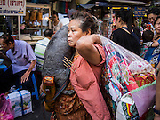 10 JANUARY 2014 - BANGKOK, THAILAND:  A woman carries her pet dog in Chinatown section of Bangkok.    PHOTO BY JACK KURTZ