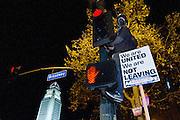 A Occupy LA demonstrator climbs a signal pole to get a better view of oncoming police at the corner of Broadway and Spring Streets in Los Angeles, Calif. on Monday, November 28, 2011. (Photo by Gabriel Romero ©2011)
