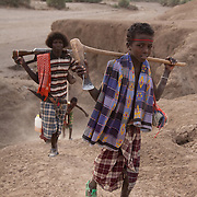 Hussein is heading back to his family and the goats with his brother Muhammed behind him. It's dry season in Afar and water is hard to come by. Here a hole has been dug into the river bed to be able to find something to drink. Both animals and humans suffer in the dry season and travel long distances to find water and grassing.  Hussein and his family are pastoralists and have come to water their goats. Action for Integrated Sustainable Development Association (AISDA) work in the AFAR region of Eastern Ethiopia, based in Delafagi. The Afars practise an old tradition of Female Genital Mutilation where the baby girls has her clitoris and labia cut away and her vagina sewn up. The day before her wedding day the girl is un-stiched ready for marriage. Its a brutal and barbaric tradition which AISDA is challenging with great effect, now more than a hundred girls in Dowe district have been saved from the knife and AISDA is now rolling out the scheme in Delafagi. Delafagi is where the oldest ever human remains have been found, the found is thought to be 4.5 mill years old.