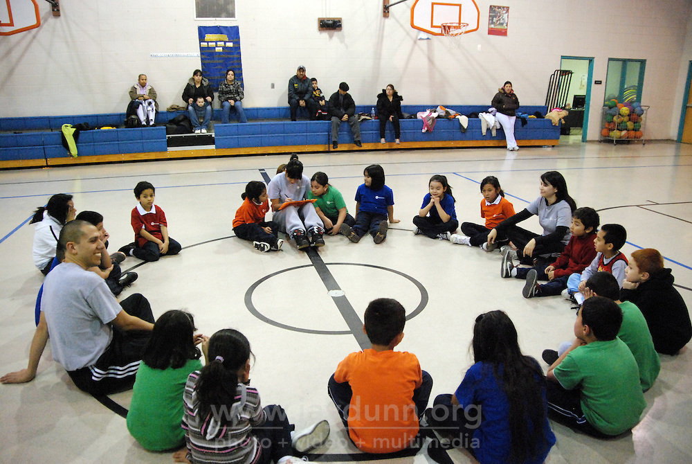 "USA, Chicago, IL, December 16, 2009.  Circle time gives thanks for good teamwork. Founded ten years ago by Rob and Amy Castaneda, ""Beyond the Ball"" is a non-profit organization dedicated to giving kids and parents a healthy place to play together, whether it be in an after-school program or during an summer series of playground days, like last year's wildly successful ""Project Play."" The predominantly working-class neighborhoods of Little Village and North Lawndale have no park, and little public space for families that is safe from the gang violence endemic to large US cities. Beyond the Ball's approach is personal, and takes a long-term view - both Rob and Amy are neighborhood residents, and have experienced first-hand the anger of gang members. The group arranges for school facilities to be open late, such as this gym at Josefa Ortiz de Dominguez Elementary, and welcomes student volunteers who also get credit from Chicago Public Schools for doing community service. Many of the teenagers working with ""Beyond the Ball"" are comfortable as mentors, because they've been in the program before. It is easy to see the pride they take in teaching and taking responsibility for the younger kids, and how such a positive approach to neighborhood building can work. Photo for Hoy by Jay Dunn."