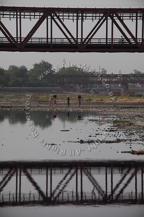 Women are walking on a bank of the heavily polluted and semi-dry Yamuna River next to the Taj Mahal, in Agra.