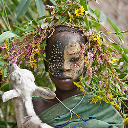 A young girl from the Mursi tribe with her goat. The goat kept eating at the girl's headdress while she was trying to pose. It made for a good laugh for everyone. <br />