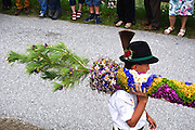 The prangstangen of Muhr, Austria, are each topped with something different: an image of the Virgin Mary, a wooden silhouette of the monstrance or, in this case a pine tree.  The pole bearers here dress in traditional costume, including lederhosen and an Alpine hat with a gamsbart (a brushy tuft of goat hair).