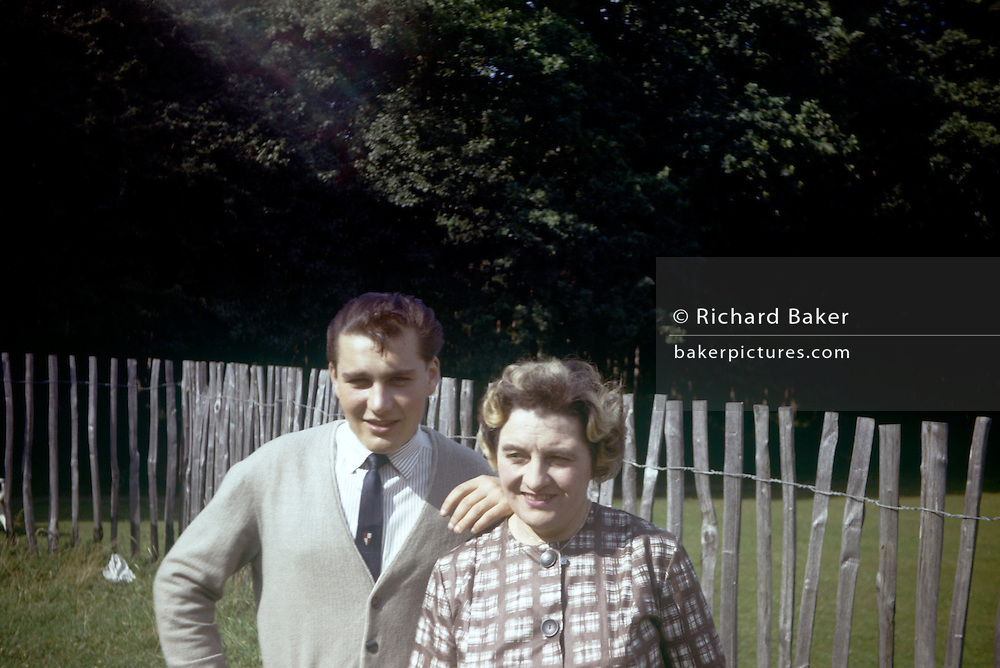 A portrait of a mother and teenage son in a public park during summer time in the early 1960s. The portrait has been recorded on a film camera by an amateur photographer in 1961. The young man stands with his arm on his mum's shoulder in this public park in Essex. The picture shows us a memory of nostalgia in an era from the last century.