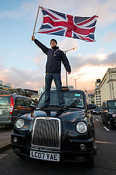 © Licensed to London News Pictures. 18/01/2018. London, UK. A Black Cab driver waves the Union Jack on the bonnet of his taxi during a blockade of London Bridge to protest against minicab firm Uber's continued operation in London. Transport for London revoked Uber's license in September 2017 but the decision is currently under appeal. Photo credit: Rob Pinney/LNP