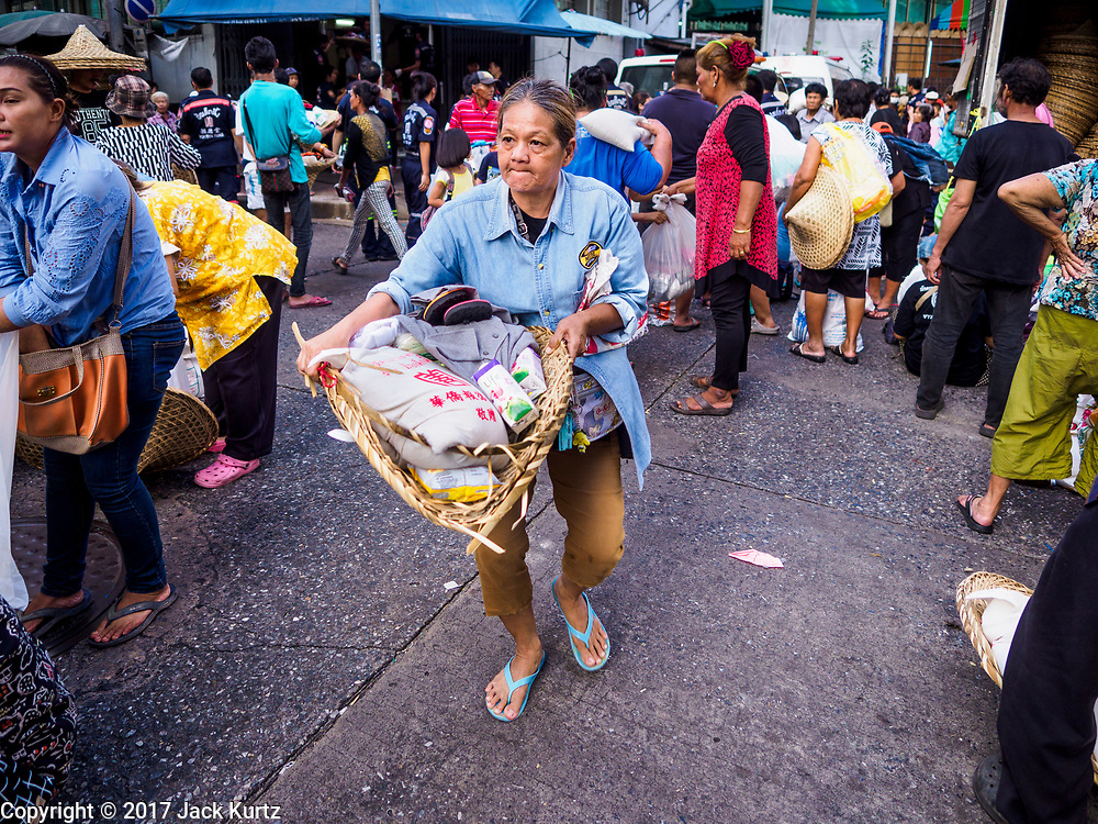 18 SEPTEMBER 2017 - BANGKOK, THAILAND: A woman carries a basket of food  home after the food giveaway at Poh Teck Tung on the last day Hungry Ghost Month. The Ghost Festival, also known as the Hungry Ghost Festival, Zhongyuan Festival or Yulan Festival is a traditional Buddhist and Taoist festival held in Asian countries. According to the Chinese calendar (a lunisolar calendar), the Ghost Festival is on the 15th night of the seventh month. In Chinese culture, the fifteenth day of the seventh month in the lunar calendar is called Ghost Day and the seventh month in general is regarded as the Ghost Month, in which ghosts and spirits, including those of the deceased ancestors, come out from the lower realm. Distinct from both the Qingming Festival (in spring) and Double Ninth Festival (in autumn) in which living descendants pay homage to their deceased ancestors, during Ghost Festival, the deceased are believed to visit the living.     PHOTO BY JACK KURTZ