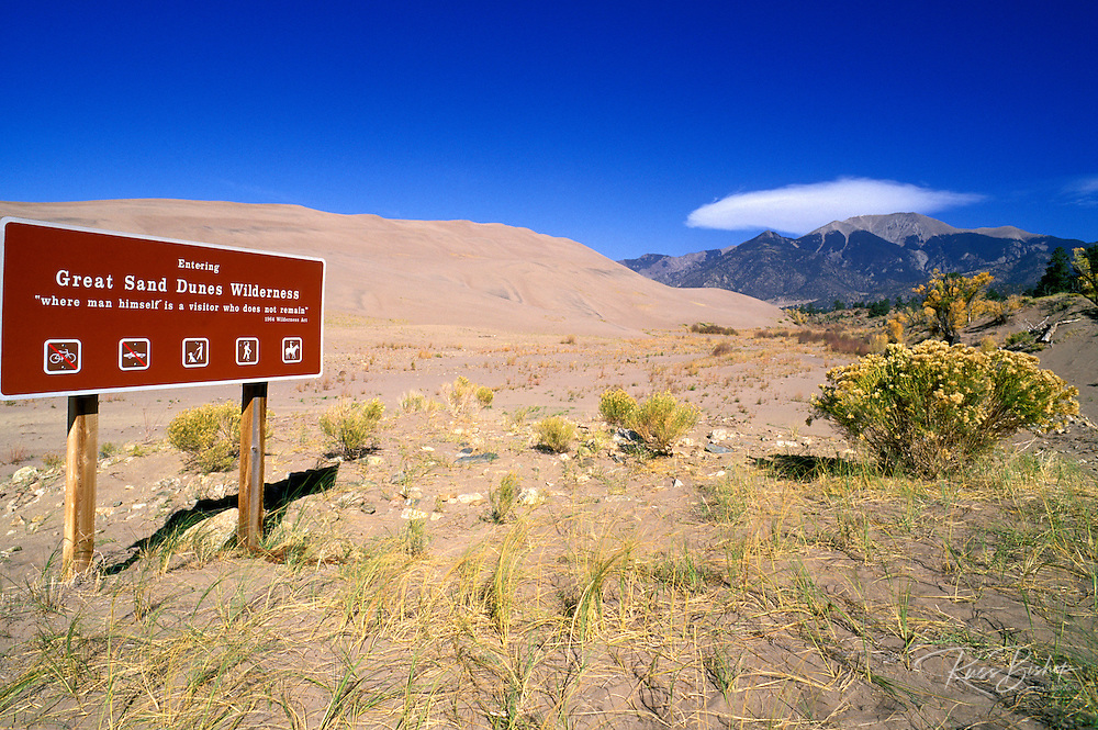 Great Sand Dunes Wilderness sign under dunes and the Sangre de Cristo Mountains, Great Sand Dunes National Park, Colorado.