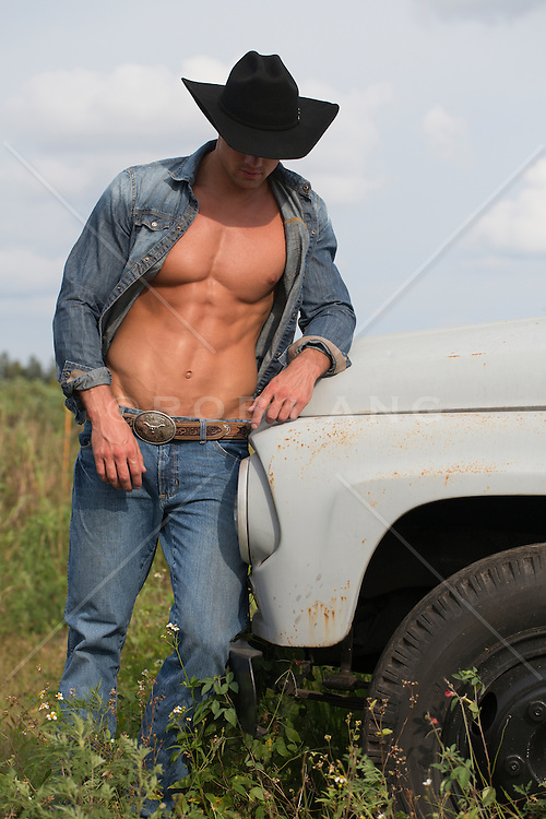 muscular cowboy with an open shirt leaning against an old pickup truck