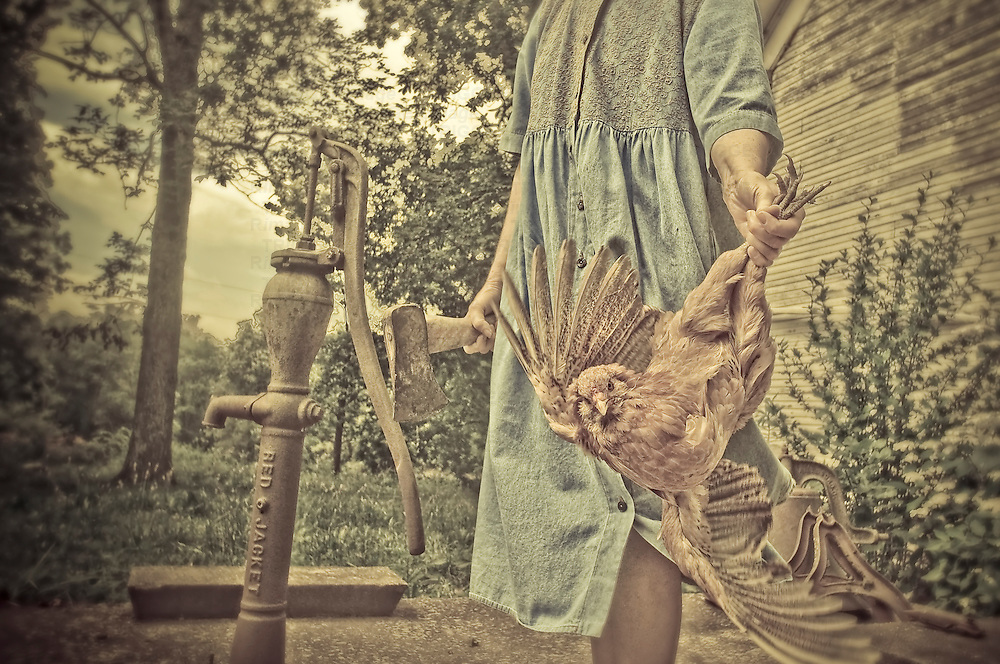 Female holding chicken by legs with axe in hand