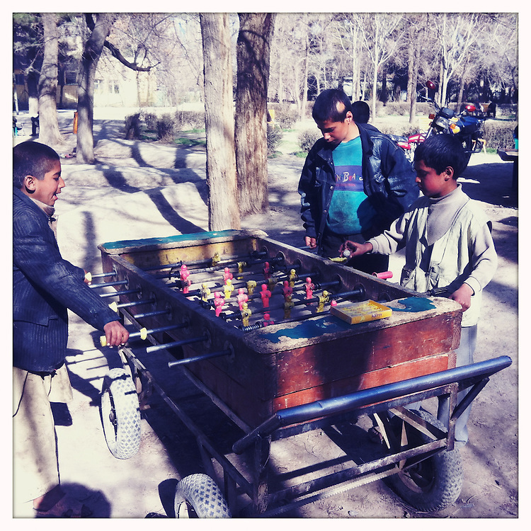 Boys play foosball in a park.