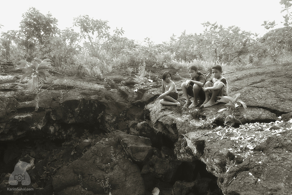 Children hanging out near a collapsed section of a lava field in Saleaula, Savai'i, Samoa.