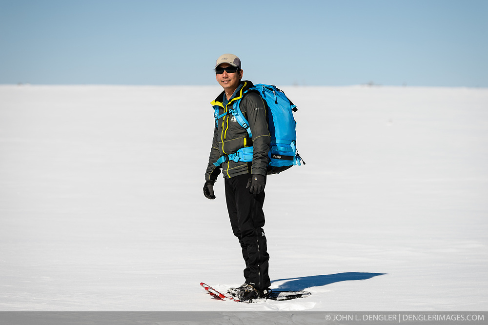 Wildlife photojournalist Noppadol Paothong poses for a photo while hiking to a lek in Wyoming. ©John L. Dengler / DenglerImages.com