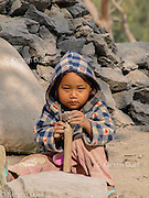 Refugees, including women and children, carry out most of the road and construction work. This small child is not exactly working but sitting in the dirt while his parents conclude a long shift