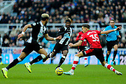 Allan Saint-Maximin (#10) of Newcastle United sends his pass beyond the outstretched leg of Jan Bednarek (#35) of Southampton towards the run of Joelinton (#9) of Newcastle United during the Premier League match between Newcastle United and Southampton at St. James's Park, Newcastle, England on 8 December 2019.