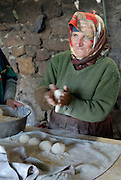 An old woman prepares dough balls for pizza in a street oven