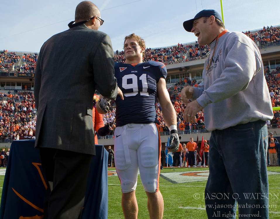 Howie Long (right) reacts after Virginia athletic director Craig Liittlepage informs Virginia defensive end Chris Long (91) that his jersey is to be the first UVA football jersey to be retired.  The #8 ranked Virginia Tech Hokies defeated the #16 ranked Virginia Cavaliers 33-21 at Scott Stadium in Charlottesville, VA on November 24, 2007.