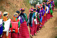 """BURMA / MYANMAR. Shan State, Kalaw- .Peinnebin Village. 2006. Women in the lead, Wan Tha?s wedding procession arrives in Peinnebin after a full day?s journey, dressed in their finest """"longyis,"""" or traditional skirts.."""