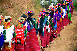 "BURMA / MYANMAR. Shan State, Kalaw- .Peinnebin Village. 2006. Women in the lead, Wan Tha?s wedding procession arrives in Peinnebin after a full day?s journey, dressed in their finest ""longyis,"" or traditional skirts.."