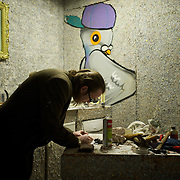 Ireland: Irish artist Frank Buckley at the kitchen in his Billion Euro House art installation in central Dublin. ..Worthless euros, taken out of circulation and shredded by Irelands Central Bank, formes the interior walls of an apartment that Mr. Buckley does not own in a building left vacant by the countrys economic ruin...The artist decided to call the apartment  built from thousands of bricks of shredded, decommissioned cash (each brick contains, roughly, what used to be 50,000 euros)  the Billion Euro House. He reckons that about 1.4 billion euros actually went into it, but the joke, of course, is that it is worth simultaneously so much and so little...A large gravestone beside the main door, announces that Irish sovereignty died in 2010, the year that the government accepted an international bailout so larded with onerous conditions that the Irish will be paying for it for years to come. (Paulo Nunes dos Santos/Polaris)