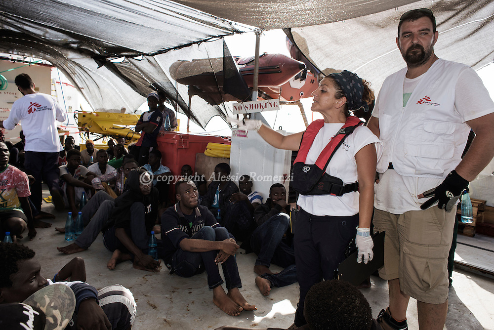 Italy: MSF Dignity1: MSF field coordinator Francesca Mancia and cultural mediator Samir Sayyad (R) give indications to African migrants rescued at sea on the forecastle deck of the Dignity1 on August 23, 2015. Alessio Romenzi