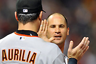 Omar Vizquel is congratulated by Rich Aurilia after Vizquel's successful suicide bunt in the ninth inning in his first game back in Cleveland.