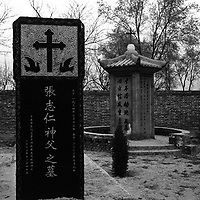 """LIUJIAZHUANG VILLAGE , APRIL 8: united on the graveyard : underground and """"official"""" priests do not share the same churches while they are alive,in Liujiazhuang village they are united on the graveyard.The black tomb in the front belongs to father Charles Zhang who left China in 1949 ,spent 15 years in Vietnam ,then moved to Rome,later to france where he met the pope in 1983.Ten years before his death he returned to China .His passport was confiscated upon his arrival and thenhe was transfered to the congregation in Liujiazhuang.China cut relations with the Vatican in the early fifites and since then, established a Patriotic catholic Church that's controlled by Chinese authorities.<br />Catholics who refused to give up their ties with the Vatican, started worshipping in underground churches and consequently were persecuted for a long time. Since the late nineties though, relations with the Vatican informally started to improve. Although China still has no diplomatic relations, many representatives from official churches met the pope John Paull II secretely . The Vatican, under the pope's leadership, has made several efforts to recover the tie with China. In February 2006 , Hong Kong Bishop Joseph Zen was named one of the first 15 new cardinals, which is seen by many as a gesture of goodwill and a significant step towards recovering the Vatican-China relationship."""