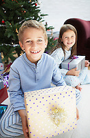 Brother and sister holding gifts sitting by christmas tree portrait