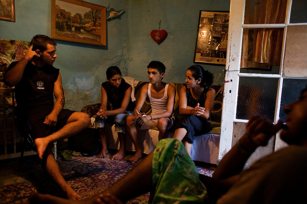 Stojan (15 years old) and his friends inside the home of an amateur tattoo artist, who was giving Stojan his first tattoo which runs the length of his left arm.