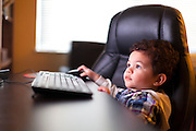 Small boy using a computer at a desk