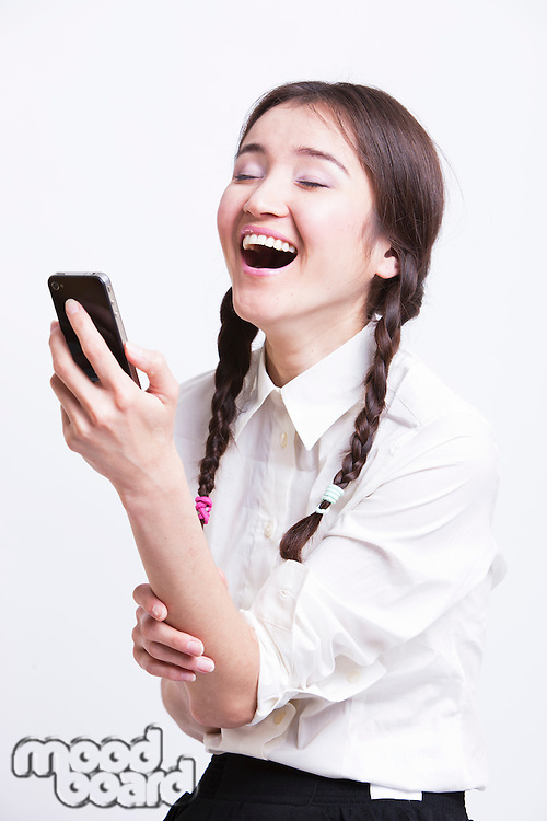 Cheerful young woman using cell phone against white background