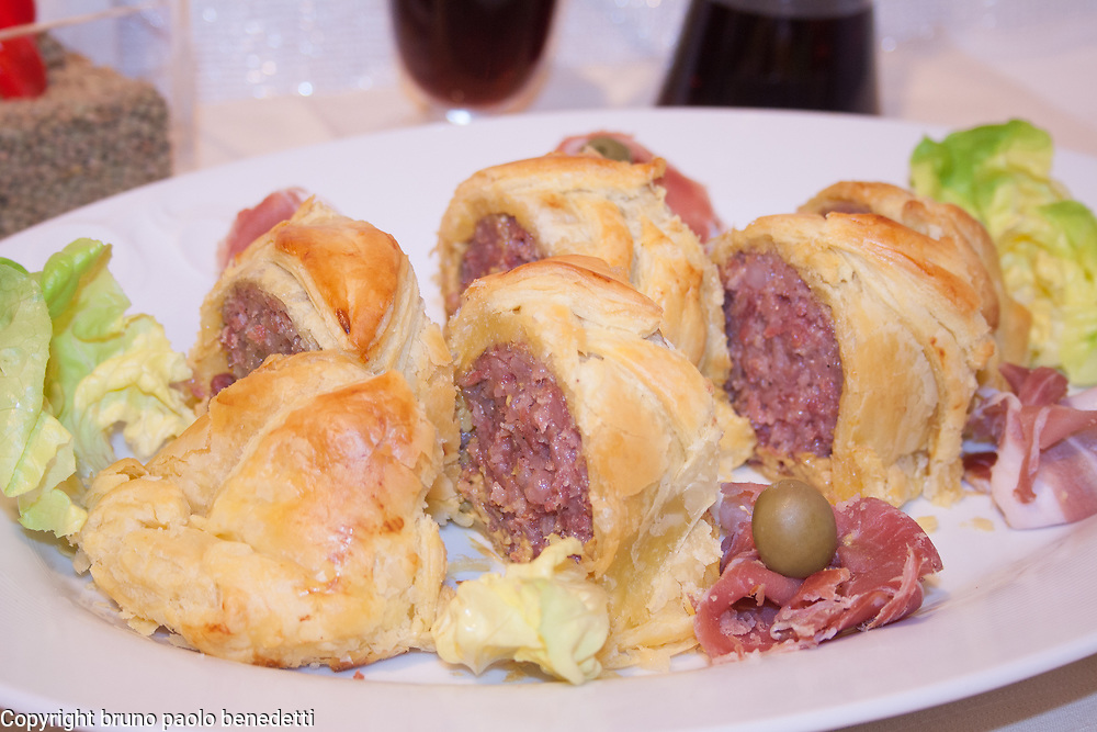 cotechino sausage in puff pastry crust, side view close-up of slices on white dish with red wine ad candle on blured backgrund, italian food