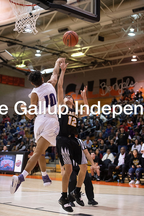 Rae Tarin (12) for Hobbs takes a shot under the basket and is blocked by Jacob Moon (10) for Clovis at the 75th Annual Gallup Boys Invitational Basketball Tournament Championship game, Saturday, Jan. 5, 2019 at Gallup High School.