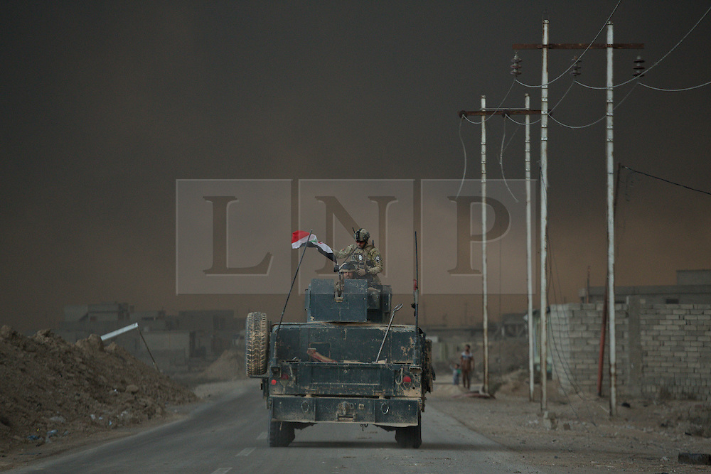 Licensed to London News Pictures. 02/11/2016. Qayyarah, Iraq. With the sky blotted out by burning oil wells, set alight by retreating Islamic State militants, soldiers of the Iraqi Army's Emergency Response Unit keep watch from the top of their armed Humvee utility vehicle as their convoy enters the town of Qayyarah, Iraq.<br /> <br /> Two months after being liberated from the Islamic State, the Iraqi town of Qayyarah, located around 30km south of Mosul, is still dealing with the environmental repercussions of their ISIS occupation. The town's estimated 15,000 inhabitants constantly live under, and in, heavy clouds of smoke which often envelope the settlement. The clouds emanate from burning oil wells in a nearby oil field that were set alight by retreating ISIS extremists after a two year occupation. The proximity of the fires, often right next to homes within the town, covers many buildings and residents with thick soot and will lead to long term health and environmental implications. Photo credit: Matt Cetti-Roberts/LNP
