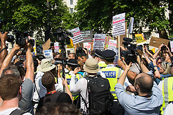 London, June 21st 2017. Protesters march through London from Sheherd's Bush Green in what the organisers call 'A Day Of Rage' in the wake of the Grenfell Tower fire disaster. The march is organised by the Movement for Justice By Any Means Necessary and coincides with the Queen's Speech at Parliament, the destination. PICTURED: The crowd push back against a police line at the gates of Downing Street.