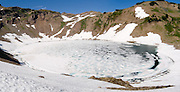 Ice covers most of Goat Lake in late July, in Goat Rocks Wilderness Area. Hike this scenic loop to Snowgrass Flat and Goat Ridge (13 miles, with 3180 feet total gain) in Gifford Pinchot National Forest, Washington, USA.
