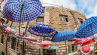 Umbrellas hanging above a narrow staircase in Amman, Jordan.