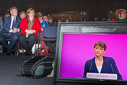 © Licensed to London News Pictures . 24/09/2014 . Manchester , UK . Ed Balls (left) in the audience listening to the Shadow Home Secretary Yvette Cooper (on monitor on the right) deliver her speech to the conference . The Labour Party Conference 2014 . Photo credit : Joel Goodman/LNP