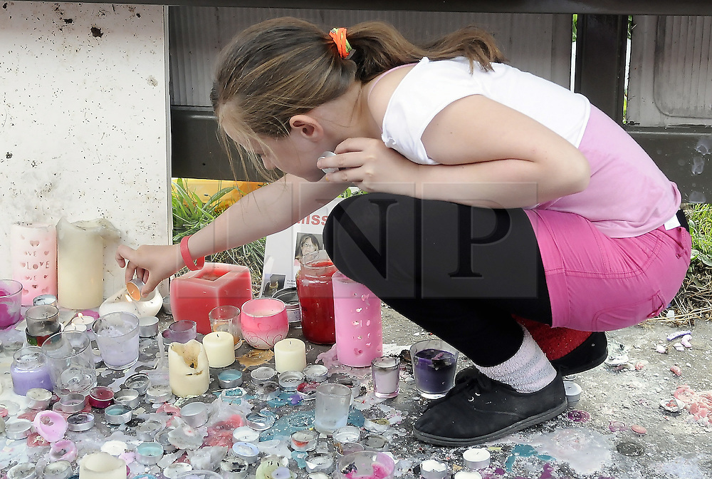 © Licensed to London News Pictures. 09/08/2012 .A girl lights a candle at the bus stop near Castle Hill School and The Lindens.. Sixth day (09.08.2012) Tia Sharp has been missing..  12 years old Tia Sharp has been missing from the Lindens on The Fieldway Estate in New Addington,Croydon,Surrey since Friday last week. .Photo credit : Grant Falvey/LNP