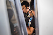 """31 MAY 2014 - BANGKOK, THAILAND: A young man sits in the back of a Royal Thai Police vehicle after he was detained for holding a sign that said """"Respect my vote"""" in a solitary protest against the military government. Bangkok was mostly quiet Saturday. There were only a few isolated protests against the coup and military government.    PHOTO BY JACK KURTZ"""