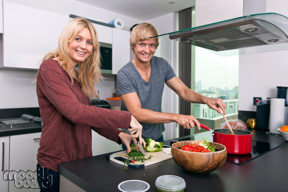 Portrait of happy Caucasian couple cooking together in kitchen