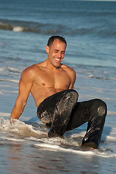 Man in jeans laughing as he gets himself up out of the surf