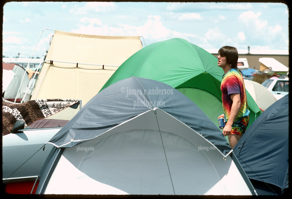 A guy seems lost or searching in a Sea of Tents. The Campground at Oxford Plains Speedway, Oxford Maine. Grateful Dead Concerts Weekend, July 2 & 3, 1988