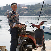 Sicilian fisherman and his motorscooter at the marina docks, Cefalu, Sicily, Italy