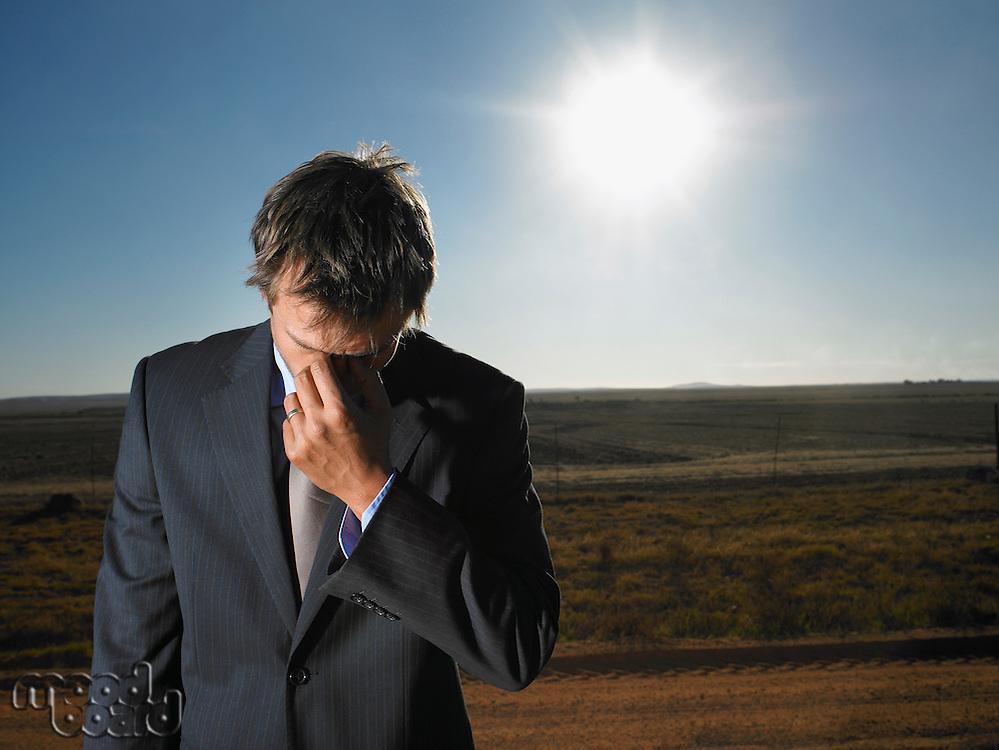 Despairing businessman in barren landscape