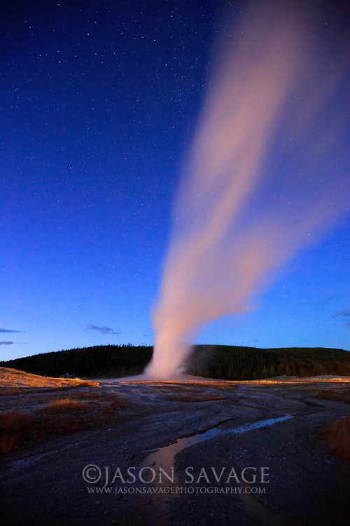 Old Faithful erupting at night, Yellowstone National Park.